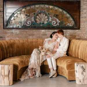 LGBTQ Couple just married on velvet yellow couch with stained glass backdrop