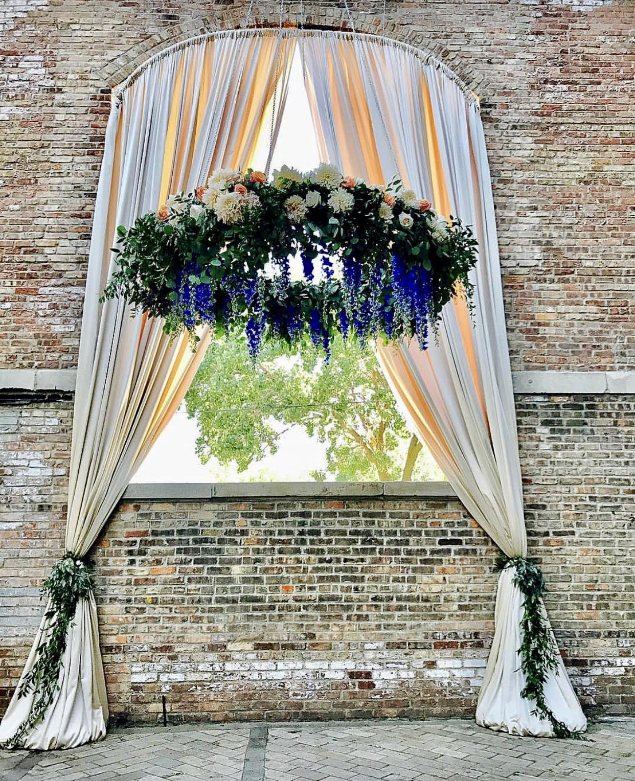 close up of larger arch draped + hanging greenery halo