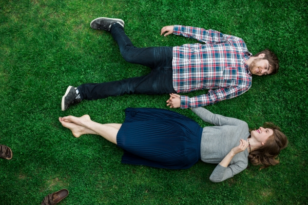 Engaged couple lying in the grass